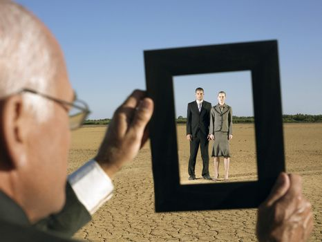 Middle aged businessman framing young business couple in desert