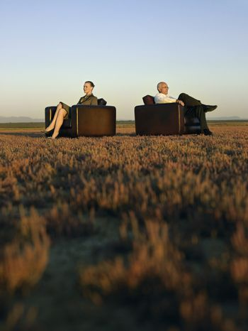 Two business people sitting in armchairs on open plain