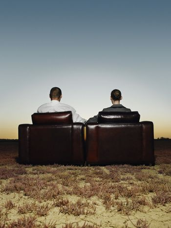 Rear view of business people sitting on leather chairs in open plain at sunset
