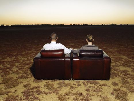 Rear view of business couple on armchairs watching sunset in open plain