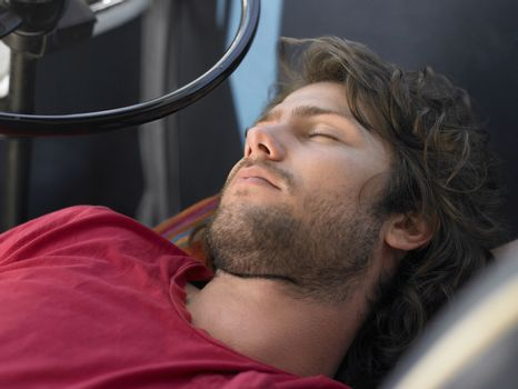 Young Man Sleeping in Vehicle head and shoulders