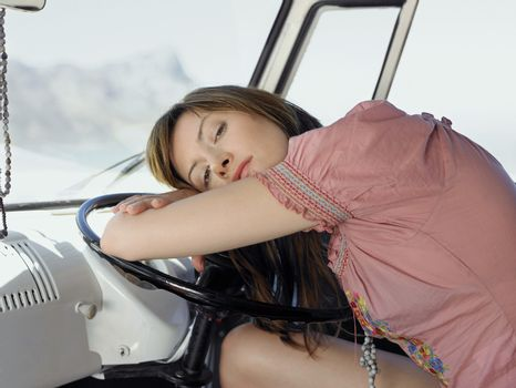 Tired young woman resting on steering wheel of van
