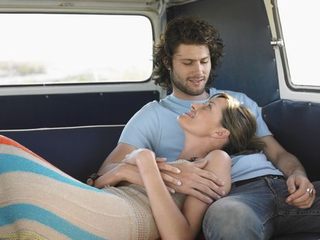 Affectionate young couple relaxing in campervan