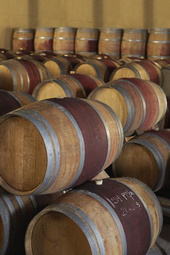 Stacked wine barrels to ferment in cellar