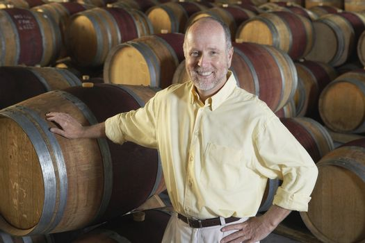Portrait of happy middle aged man leaning on wine cask in cellar