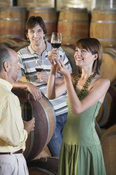 Three people tasting wine beside wine casks in cellar