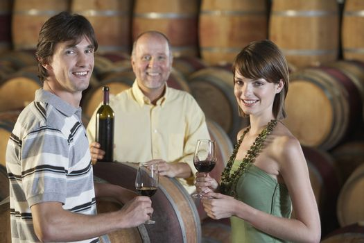 Portrait of young couple holding glasses of red wine with merchant in cellar
