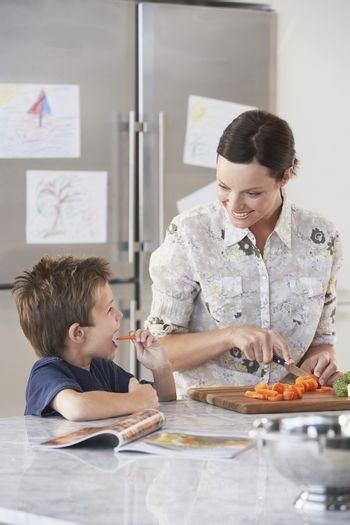 Happy mother chopping carrot while son eating at domestic kitchen