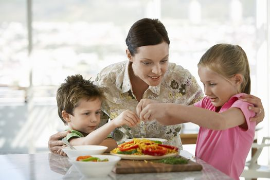 Happy mother helping children to prepare meal in kitchen