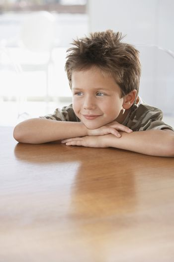 Young Boy with His Head on hands resting on the Table