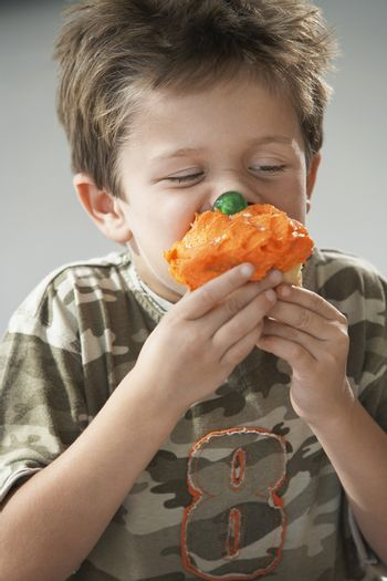 Young boy eating cup cake isolated on gray background
