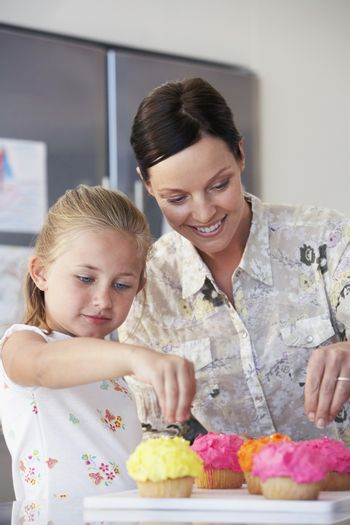 Happy mother and daughter decorating cupcakes in kitchen