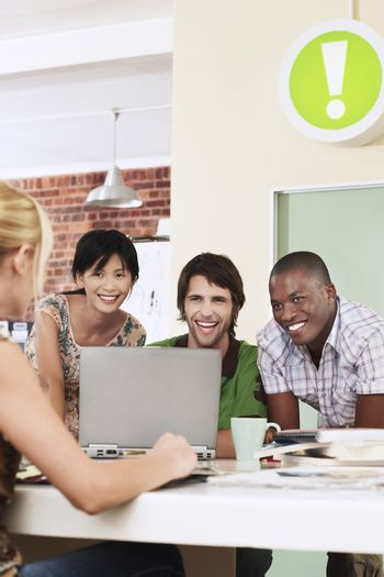 Group of cheerful multiethnic business people using laptop in meeting room