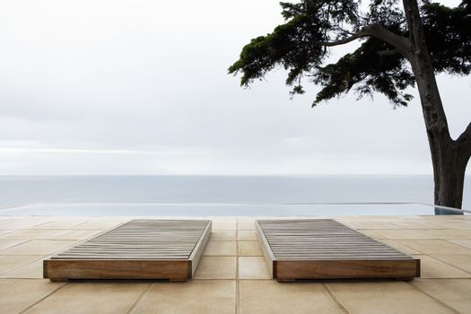 Two sun beds by infinity pool overlooking sea