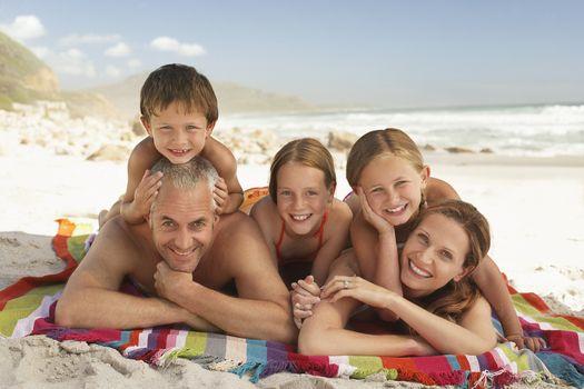 Family lying on beach.