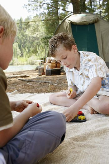 Boy sitting at campsite playing toys with brother
