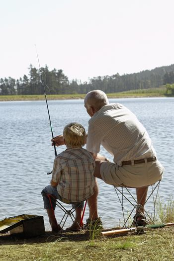 Rear view of grandfather and grandson fishing by lake