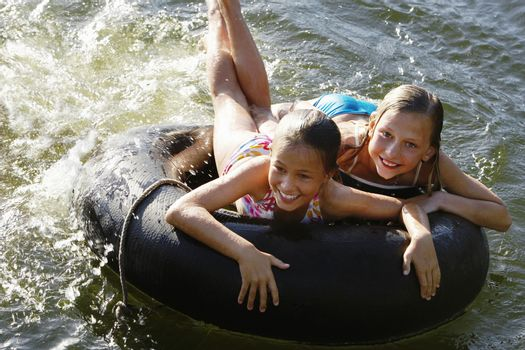 Happy young girls lying on float tube at lake