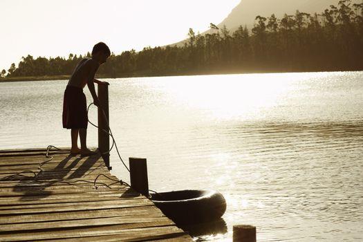 Full length of boy pulling in float tube on dock
