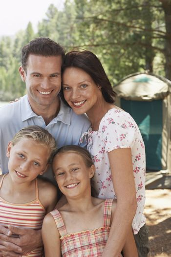 Portrait of happy parents with daughters at campsite