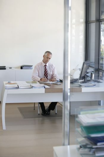 Middle aged businessman working at office desk