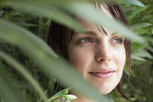 Closeup of beautiful young woman hiding in foliage