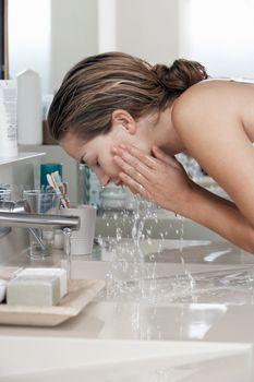 Woman washing face in bathroom