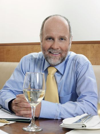 Portrait of a happy businessman with wineglass at restaurant table