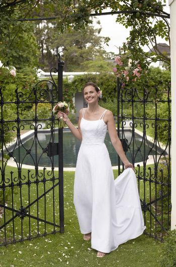 Full length of a Caucasian bride standing at the entrance gate
