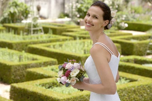 Portrait of beautiful young bride with bouquet of roses in formal garden