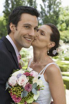 Beautiful Caucasian bride kissing groom on their wedding