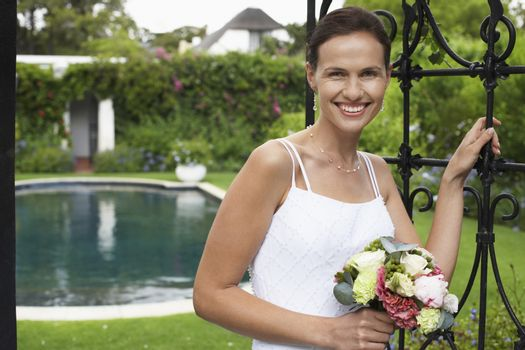Portrait of a Caucasian bride standing at the entrance gate