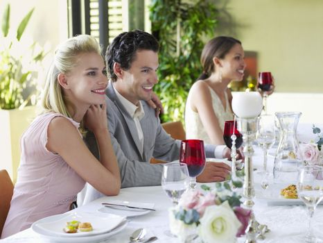 Beautiful young couple with arm around at dinner party