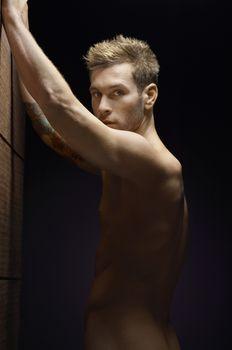 Portrait of a naked man over black background