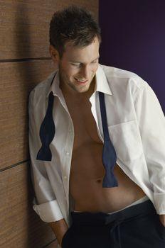 Smart Caucasian man wearing unbutton shirt with neck bow around his neck