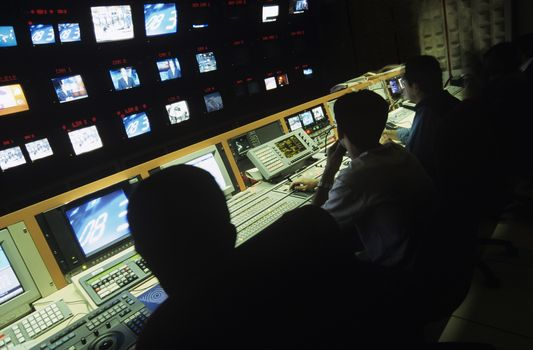 Rear view of operators in central control room at television station