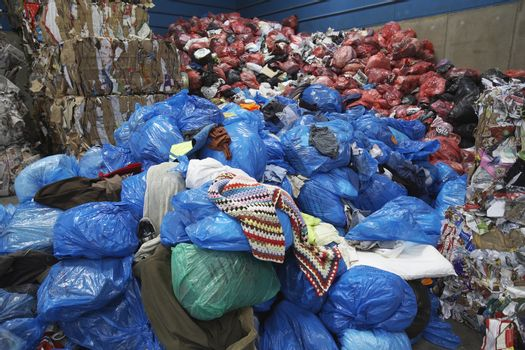 Piles of rubbish bin bags at recycling plant