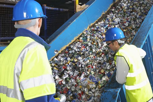Two workers monitoring conveyor belt of recycled cans in industry