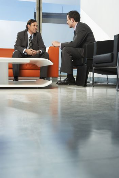 Two businessmen having meeting in office lobby
