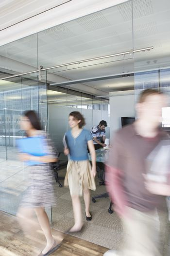 Full length of blurred office workers leaving conference room