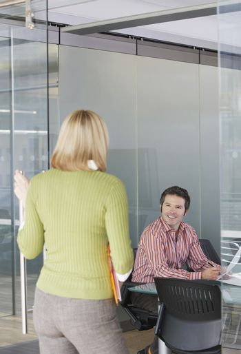 Male and female office workers talking in the office