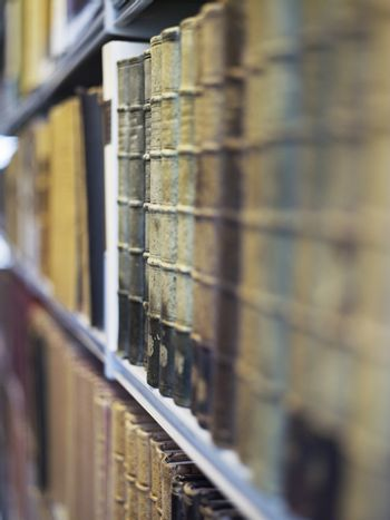 Closeup of antique books in a row on shelf