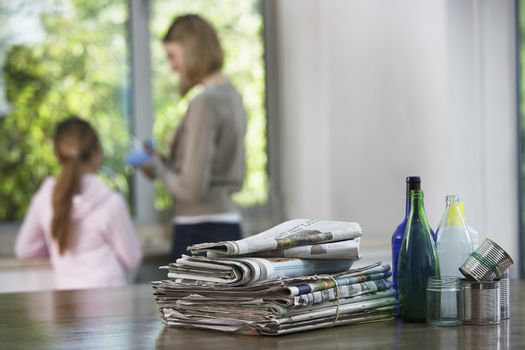 Recycling material on kitchen table with family in background