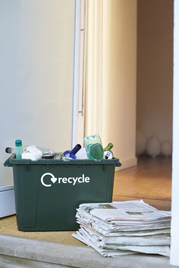 Closeup of recycling container and pile of waste papers on floor
