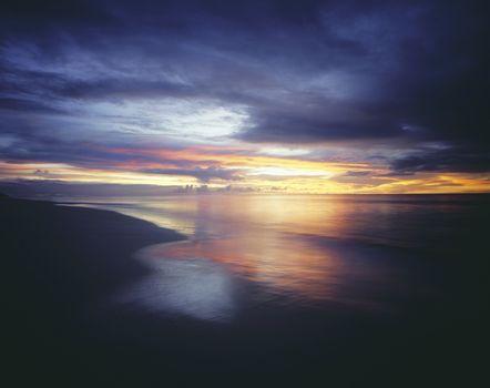 Sunset and Overcast Sky Over Beach