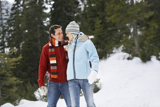 Couple walking on snow-covered path