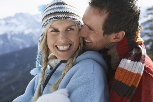 Couple embracing on mountain peak side view portrait