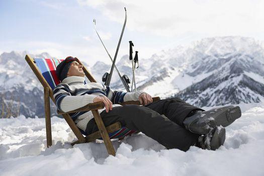 Skier resting on deckchair in mountains