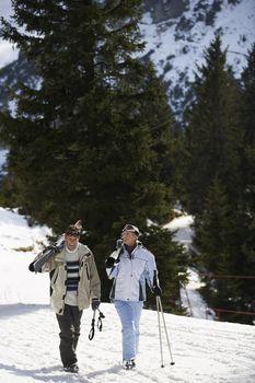 Skiing couple walking carrying skis on shoulders on ski slope