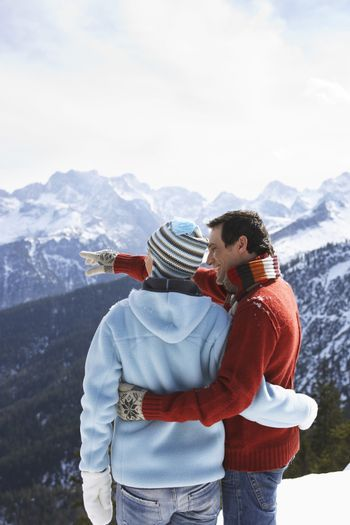 Rear view of a couple looking at view from mountain peak